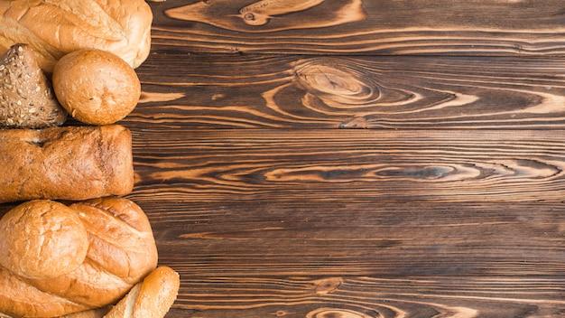 木製の背景においしい焼きたてのパン 無料写真