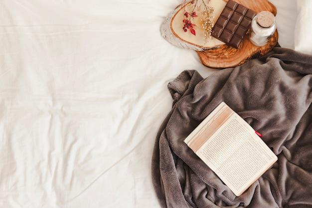チョコレートバーの近くに開いた本と毛布 無料写真