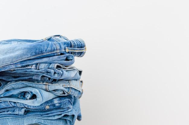 白い背景に積み重ねられた青のジーンズ 無料写真