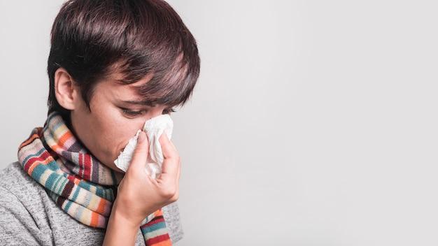 灰色の背景に対してティッシュペーパーの鼻を吹く彼女の首の周りにスカーフを身に着けている病気の女性 無料写真