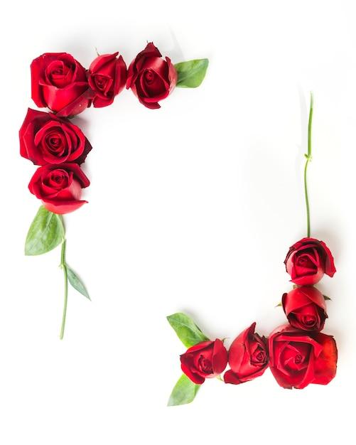 白い背景に装飾された赤いバラで作られたフレーム 無料写真