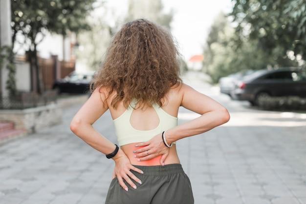 腰痛を持つ通りに立っている女性のリアビュー 無料写真