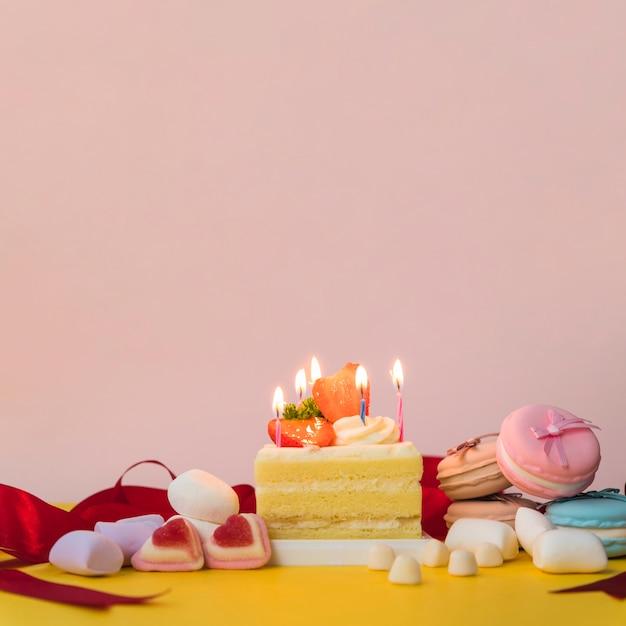 キャンディーで飾られたケーキ;マシュマロ、マカロン、黄色の机 無料写真