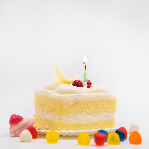 白い背景のプレートにケーキのスライスとカラフルなキャンデー 無料写真