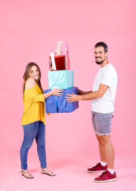 ピンクの背景にカラフルなギフトボックスを保持している若いカップル 無料写真