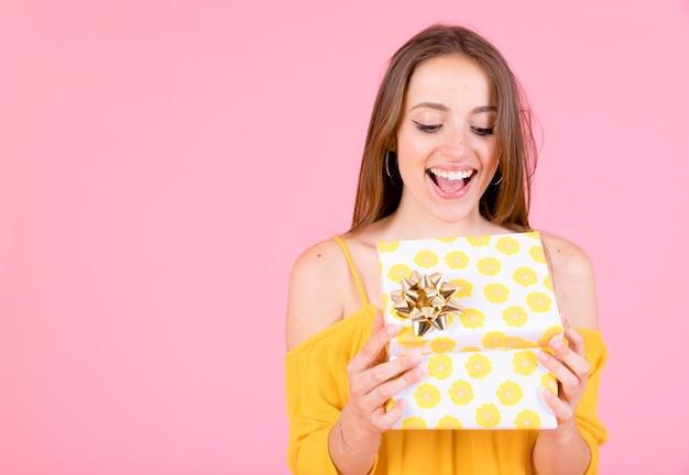 金色の弓と黄色の水玉のギフトボックスを開く興奮した若い女性 無料写真