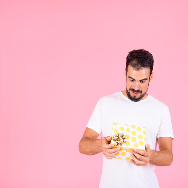 Потрясенный молодой человек, глядя на открытую подарочную коробку с золотой лук Бесплатные Фотографии