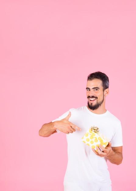 Улыбающийся человек указывая пальцем показывает подарочной коробке с золотой лук Бесплатные Фотографии