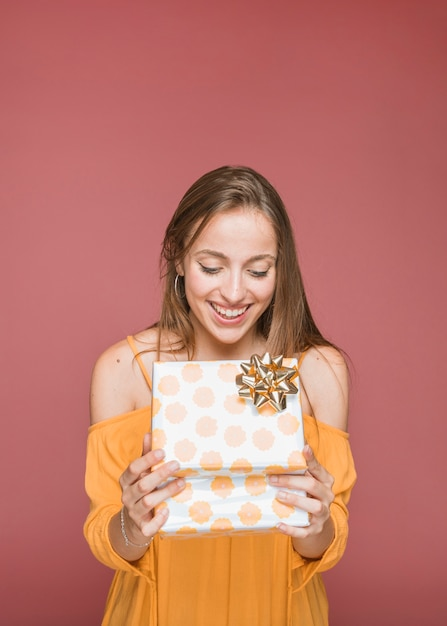 Портрет улыбающейся молодой женщины, глядя на открытую подарочную коробку Бесплатные Фотографии
