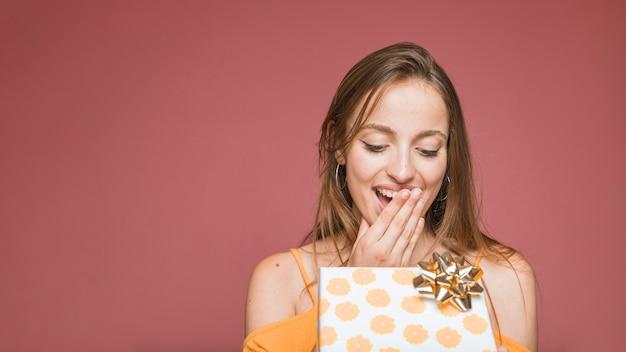 Крупный план удивленная женщина, глядя на открытую настоящую коробку Бесплатные Фотографии