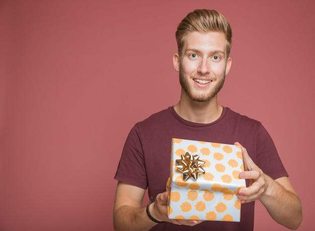 Улыбаясь человек, холдинг обернутый подарочной коробке против цветного фона Бесплатные Фотографии