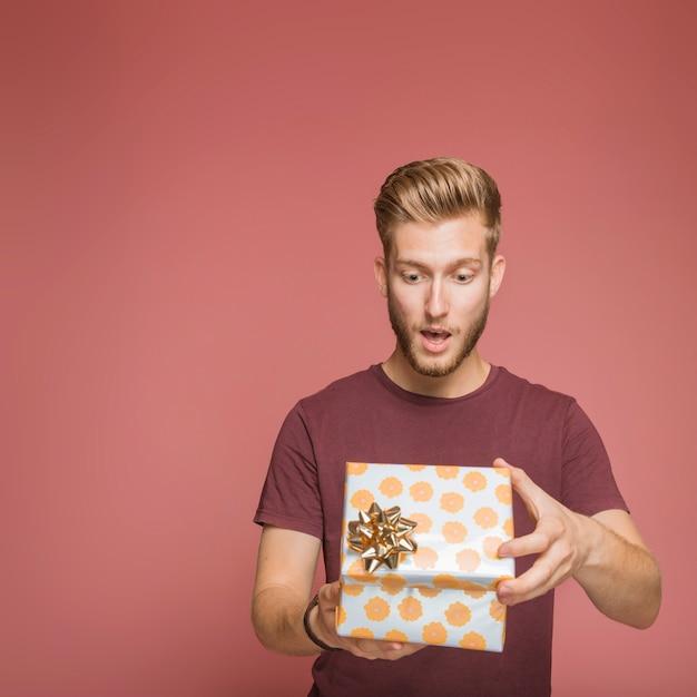 Удивленный молодой человек, открытие цветочные подарочной коробке с золотой лук Бесплатные Фотографии