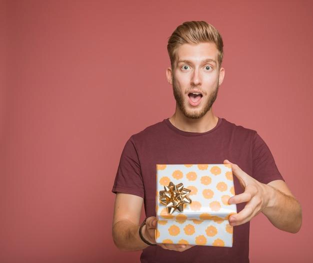 Потрясенный молодой человек, открытие цветочные подарочной коробке с золотой лук Бесплатные Фотографии