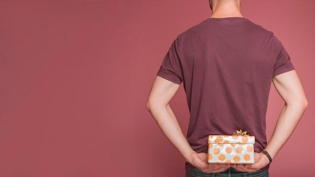 Вид сзади человека, скрывающего цветочные подарочной коробке против цветного фона Бесплатные Фотографии
