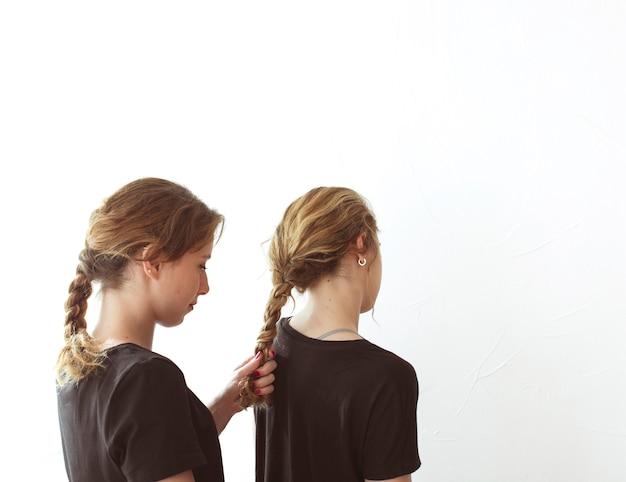 Молодая женщина, связывая волосы ее сестры, изолированных на белом фоне Бесплатные Фотографии