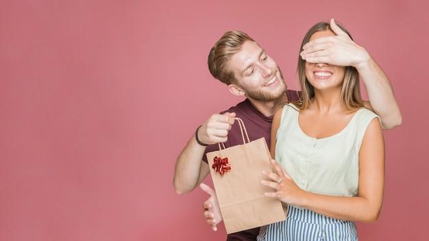 買い物袋を持つ彼女のガールフレンドの目を覆う若い男を笑顔 無料写真