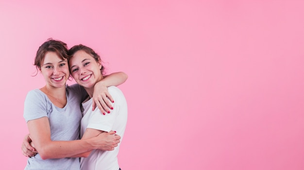 ピンクの背景の上にお互いを抱擁の姉妹の肖像画 無料写真