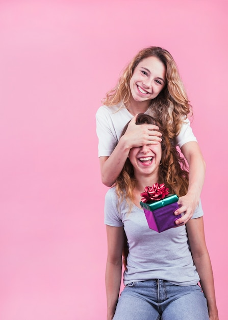 ピンクの背景に対して彼女の妹にギフトボックスを与える幸せな女性 無料写真
