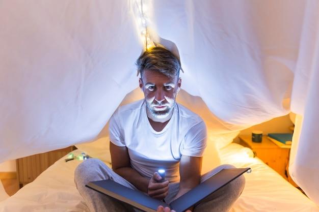 写真のアルバムを持っている顔の上にベッドの雷の懐中電灯でカーテンの下に座っている若い男 無料写真