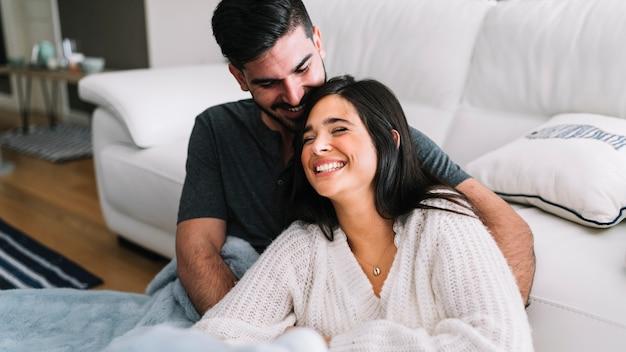 ソファの近くでお互いを愛している若いカップルに笑顔 無料写真