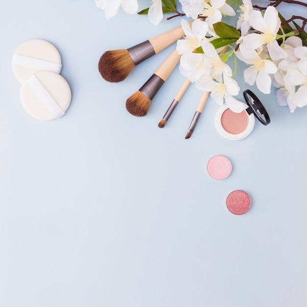 異なるタイプの化粧ブラシ;スポンジ;アイシャドー、青い背景に白い花が咲く 無料写真