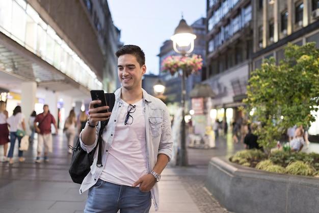 携帯電話の画面を見て笑顔の男 無料写真