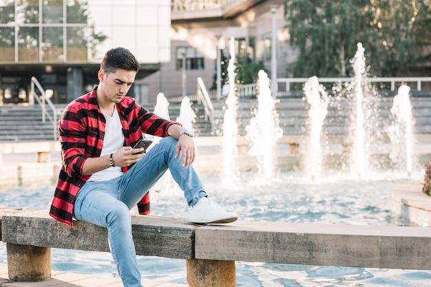 携帯電話を使って噴水の近くに座っている男 無料写真