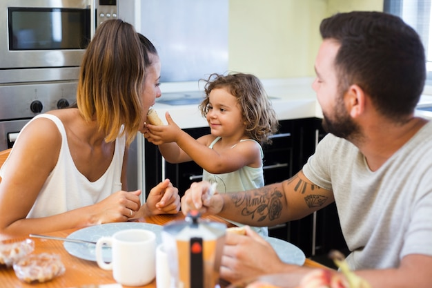 彼女の母親にパンを食べる少女を見ている男 無料写真