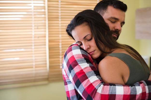 彼の妻を自宅で抱きしめている男 無料写真