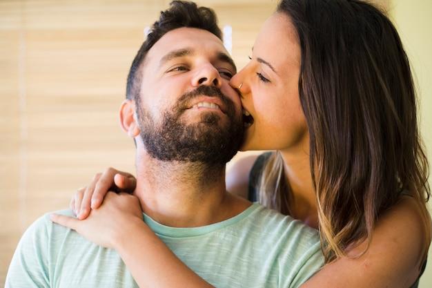 彼女の夫の頬を噛む女性のクローズアップ 無料写真