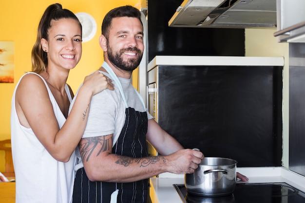 Портрет счастливая пара приготовления пищи на кухне Бесплатные Фотографии