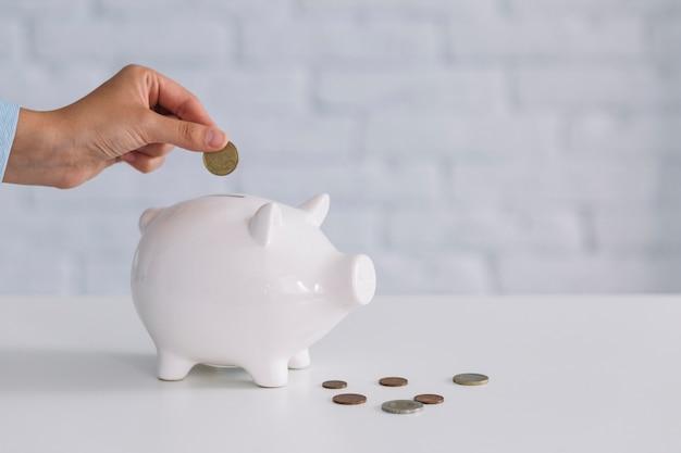 人の手は、コインを机の上の白いピギーバンクに挿入します。 無料写真