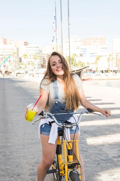 自転車に乗っているジュースのガラスで幸せな若い女性の肖像 無料写真