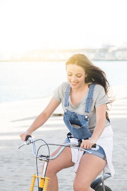 笑顔の若い女性乗馬の自転車 無料写真