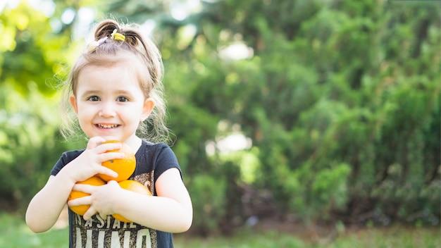 Улыбается девушка, проведение свежих апельсинов в парке Бесплатные Фотографии