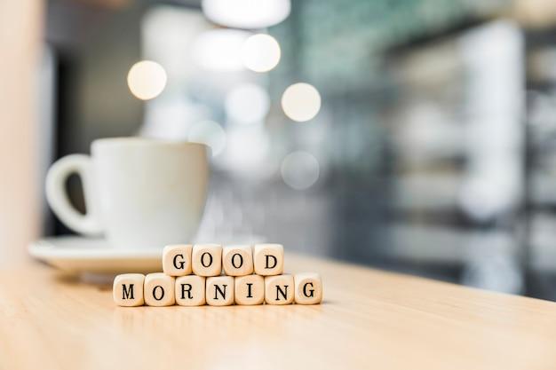 木製の机の上にコーヒーのカップとおはよう立方体ブロック 無料写真
