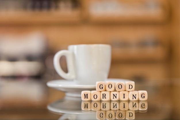 おはよう立方体ブロックと反射ガラスの机の上にコーヒーカップ 無料写真