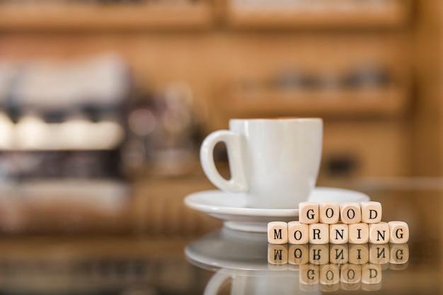 ガラスのカウンターでコーヒーのカップとおはようの木製ブロック 無料写真
