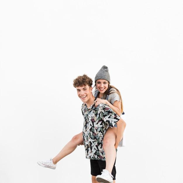白い背景に彼のガールフレンドにピギーバックを与える幸せな男 無料写真