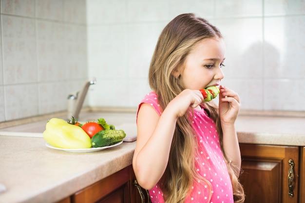 Крупный план девочка, есть салат шашлык, стоя на кухне Бесплатные Фотографии