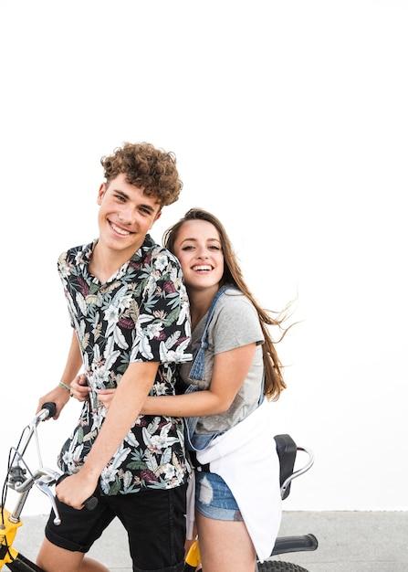 自転車に乗って楽しむ笑顔の若いカップルの肖像 無料写真