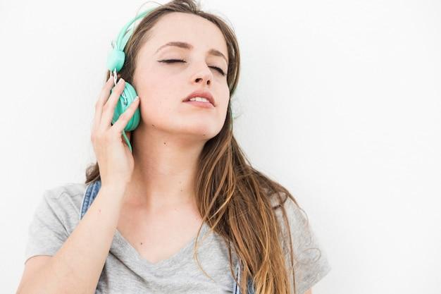 女の子、聞くこと、楽しむこと、音楽、ヘッドホン、白い背景 無料写真