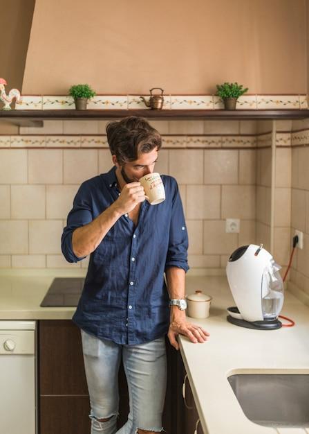 キッチンでコーヒーを飲んでいる男 無料写真