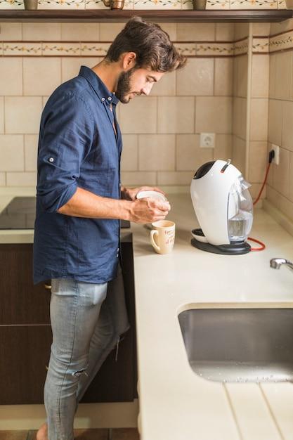 コーヒーを準備するキッチンに立っている若い男 無料写真