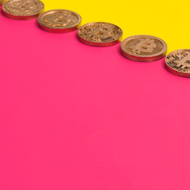 Ряд многих биткойнов над желтым и розовым двойным фоном Бесплатные Фотографии