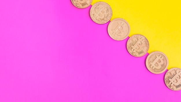Ряд биткойнов над розовым и желтым двойным фоном Бесплатные Фотографии