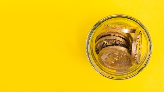 Биткойны в стеклянной банке на желтом фоне Бесплатные Фотографии