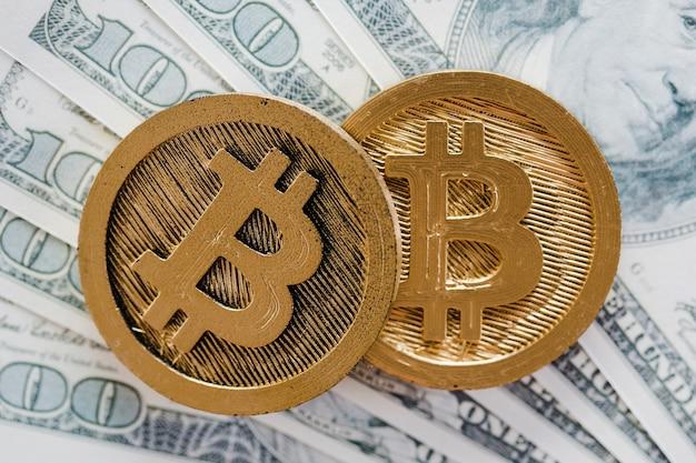Два биткойна над долларовыми банкнотами Бесплатные Фотографии