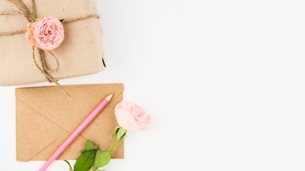ギフト用の箱;エンベロープ;色鉛筆と白い背景にバラの花 無料写真
