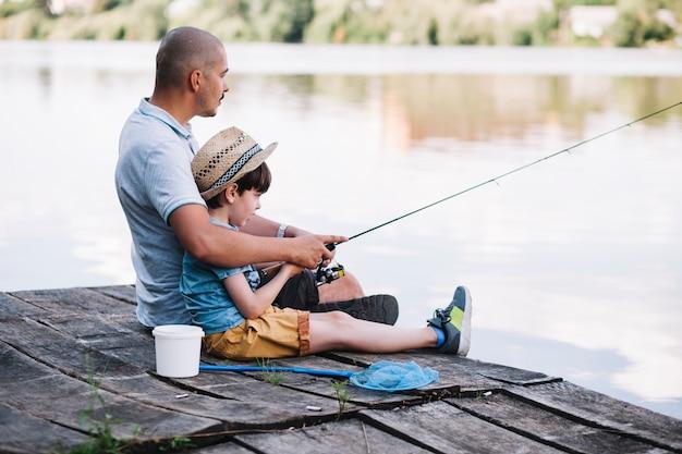 湖で釣る彼の息子と桟橋に座っている漁師の側面図 無料写真